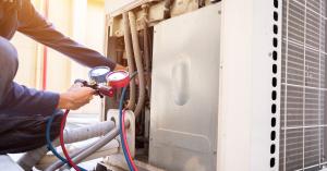 HVAC technician performing maintenance on an AC unit