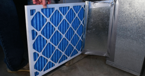 A pleated AC filter being installed into a ventilation system